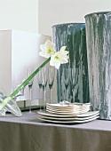 Tellerstapel Gläser und Blume in der Vase