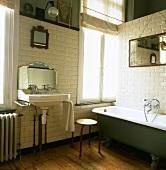 Traditionelles Badezimmer mit antikem Badezimmerspiegel und Waschbecken und einer freistehenden Badewanne