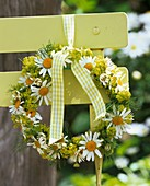 Wreath of spring flowers on chair back in garden