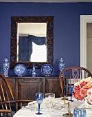Festlich gedeckter Tisch in blauem Esszimmer mit chinesischer Porzellansammlung und antiken Möbeln