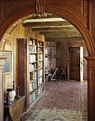 Antique, rustic hall with bookcase and brick floor