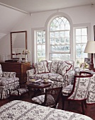 Large lattice window and furniture with matching upholstery in traditional living room