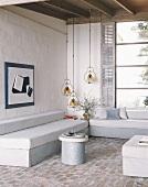 Wohnzimmer mit raumhohem Fenster mit Fensterladen, Ziegelsteinboden und zwei einfachen Sofas mit Ecktisch