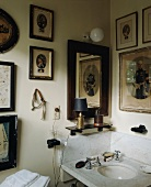 Collection of antique pictures above marble sink in corner of bathroom