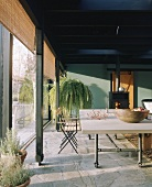 Heavy dining table on castors next to glass wall with bamboo roller blinds; black wood burner and lush house plant in background