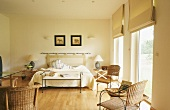 Tranquil bedroom furnished with natural materials with Roman blinds on floor-to-ceiling windows