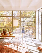 Light-flooded dining room with glass wall and view into autumnal woodland