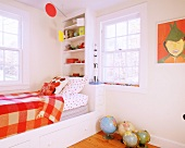 Cheerful child's bedroom with built-in bed frame, wall-mounted shelves and bright orange accents