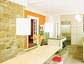 Sunny dining room with stone wall, long dining table, metal chairs, pendant lamps and section of wall in bright orange