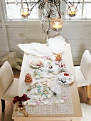 A view of a table laid for Christmas decorated with angel wings, Christmas biscuits and cake and festive decorations
