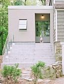Steps leading to open front door with Dalmatian sitting in doorway