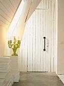 Einfache Brettertür mit langem Handgriff in einem Holzhaus; daneben ein gelber Kerzenleuchter