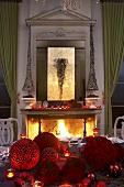 Festliche Tischdekoration; dahinter ein loderndes Feuer im offenen Kamin