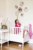 Lachendes Mädchen in ihrem Kinderbett zeigt auf lustige, runde Bilder