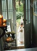 Mädchen in weißem Kleid steht vor der offenen Haustür