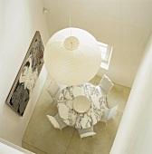 Essraum mit rundem Marmorstisch und weissen Stühlen aus der Vogelperspektive