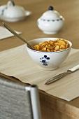 Holztisch mit Tischset und gefüllter Müslischale mit Micky Mouse Motiv