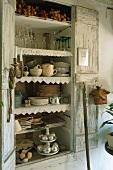 An open wooden cupboard containing crockery