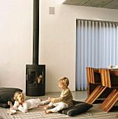 Two children in front of log burner