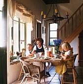Mutter & zwei Kinder beim Frühstück in ländlichem Wohnraum