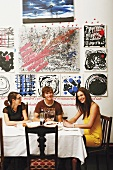 Three young people at dining table below modern artworks on wall