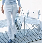 Woman carrying folded garden chair