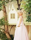 Little girl wearing long pink dress in garden