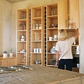 Woman in front of kitchen shelves holding crockery & utensils