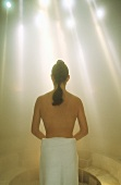 Woman wrapped in towel in steam room