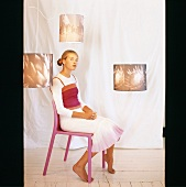 Girl sitting on pink chair
