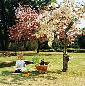 Little boy playing in garden under flowering tree