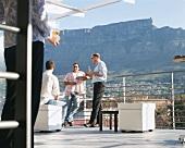 Menschen trinken Cocktails auf einer Terrasse