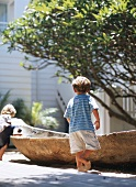 Boys playing in sand around dugout canoe