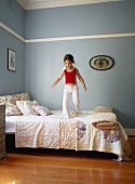 Little girl bouncing on bed