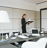 Frau steht im Büro vor Schreibtisch & blättert in einem Ordner