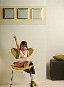 A little girl sitting cross-legged on a chair