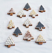Various decorated Christmas tree biscuits with icing sugar