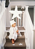 A girl sitting on a flight of stairs holding a Christmas star