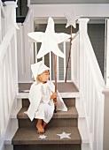 Mädchen sitzt auf einer Treppe und hält Weihnachtsstern