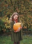 Mädchen steht im Garten und hält einen Kürbis in den Armen