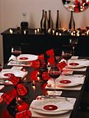 Einladend gedeckter Holztisch zu Halloween mit Rotweingläsern, Kerzenlicht und Lampions