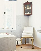 Mosaikgefliestes Badezimmer mit Eckvitrine, goldenem Stuhl und dekorativen Voluten
