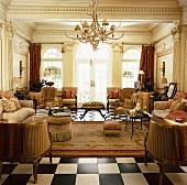 Prunkvoller, antik gestalteter Wohnraum mit diversen Sitzmöbeln, Geweihkronleuchter und Schachbrettboden