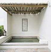 Orientalisch anmutendes Wasserbecken im Aussenbereich mit rustikaler Holzüberdachung