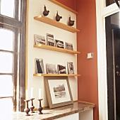 Einfache Wandregale aus Holz mit Fotos, Figuren und Kerzenständern