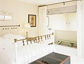 Schlafzimmer mit altem Metallbett und Ankleideraum hinter einem Vorhang