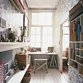 Arbeitszimmer mit raumhohem Fenster und floraler Motivtapete