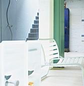 Ein tiefer Stuhl und ein kleines Schränkchen in Weiß