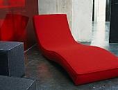 Rote Polsterliege Uund graue Würfelhocker in einem Industriegebäude