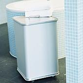 Wäschebehälter aus Aluminium in einem türkis gekachelten Badezimmer